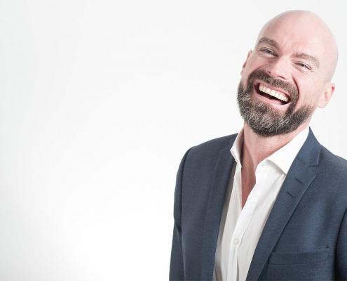 Mann mit Glatze, der unbeschwert lacht